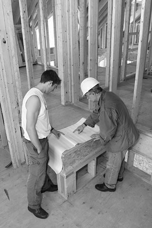 building contractor discussing plans with carpenter